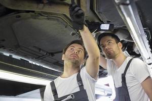 mannelijke mechanica die auto in workshop onderzoeken