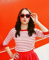 Portrait of pretty woman in red sunglasses blowing lips