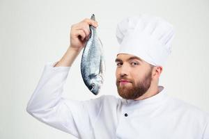 Handsome male chef cook holding fish photo
