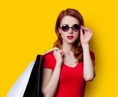 chica en vestido rojo con bolsas de compras