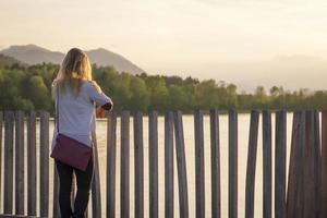 vrouw die zonsondergang bij meer bekijkt