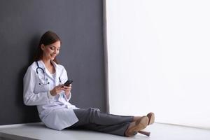 joven doctora sentada en el suelo con su teléfono