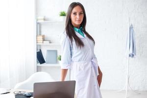 Retrato de joven doctora con bata blanca de pie en foto