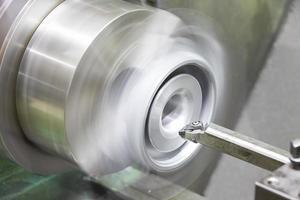 operator turning automotive parts by cnc lathe