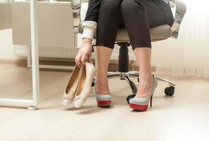 photo of businesswoman changing shoes under table
