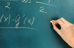 Math formula written on blackboard with chalk.