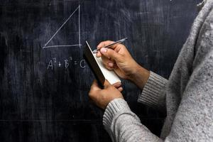Hombre tomando notas del teorema de matemáticas en la pizarra