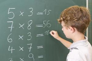 Young boy doing math lesson sums on blackboard