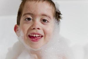 Retrato de niño sonriente mientras se baña burbujas.