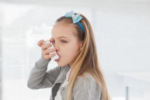 pequeña niña usando su inhalador foto