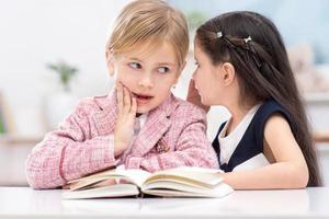 Two little cute girls whispering secrets photo