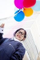 pequeño niño asiático lindo del negocio que sostiene el globo foto
