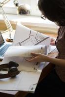 mujer trabajando en casa con laptop y plan de arquitectura