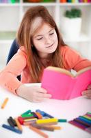 cute little red-haired girl reading a book photo