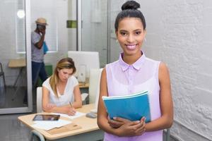 Casual woman with colleague behind in office