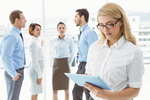 Businesswoman using digital tablet with colleagues behind