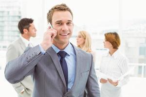 empresario mediante teléfono móvil con colegas detrás foto