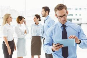 Businessman using digital tablet with colleagues behind