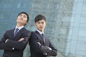 Two young businessmen outside glass building, portrait photo