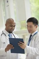 Two doctors consulting over medical record in the hospital photo