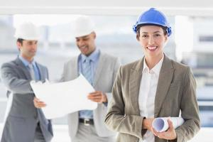 glimlachende architect met erachter team