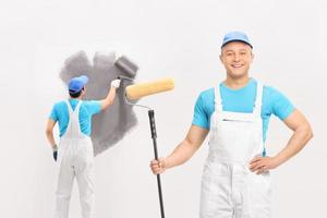 Two male painters painting a wall
