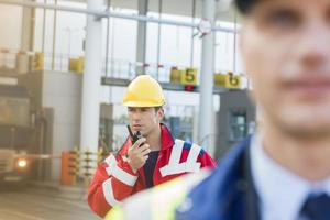 Male worker using walkie-talkie with colleague in foreground at shipyard photo