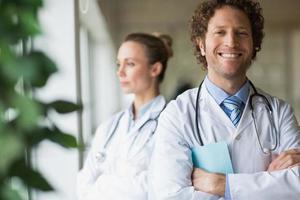 sorrindo médico em pé braços cruzados
