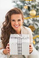 Smiling woman holding present box in front of christmas tree