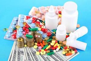 Prescription drugs on money background representing rising health care costs photo