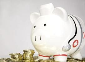 Alcancía médico tomando su dinero para atención médica y medicina foto