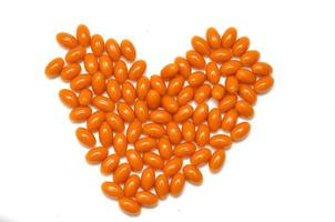 Pastillas de naranja en forma de corazón sobre fondo blanco. foto