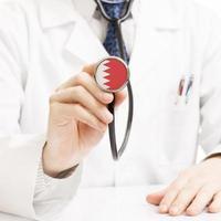 Doctor sosteniendo estetoscopio con serie de bandera - Bahrein foto