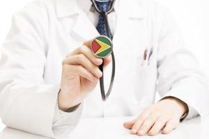 Doctor sosteniendo estetoscopio con serie de bandera - Guyana foto