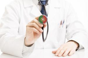 Doctor sosteniendo estetoscopio con serie de bandera - Portugal foto