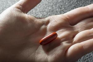 Bare hand holding one red medicinal tablet photo