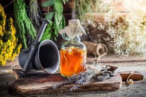 hierbas terapéuticas en botellas con hierbas y alcohol foto