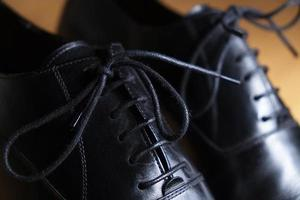 Lace detail of a pair of classic black leather shoes