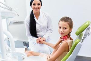 Dentista y paciente en consultorio. niño en sillón dental foto
