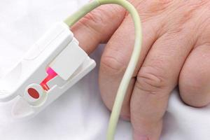 Hand of seriously ill with oxygen saturation sensor saturation. concept of illness