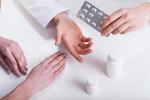 Doctor giving patient medicines closeup