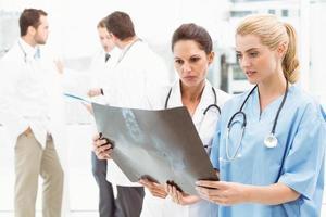 Female doctors examining x-ray photo