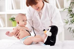 Smiling doctor pediatrician playing and enjoy with baby patient