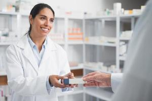 Smiling pharmacist giving a box to doctor photo