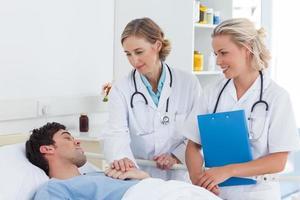 médicos de duas mulheres cuidando de um paciente