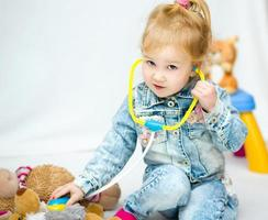 Cute little girl is playing doctor photo