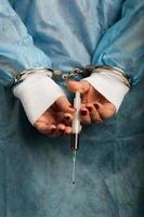 criminal médico esposado con inyector ensangrentado en la mano