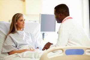Doctor hablando con paciente femenino en la habitación del hospital