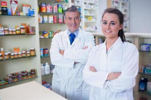 Smiling pharmacist and his trainee with arms crossed photo