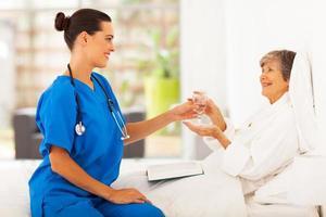 verzorger brengt water naar senior vrouw